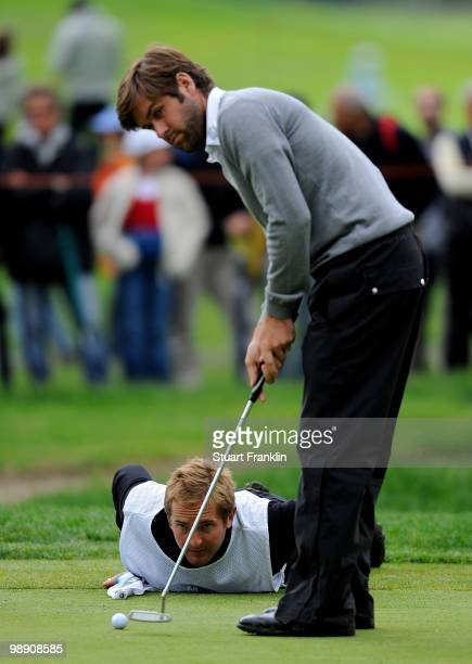 Robert Rock of England and caddie line up his putt on the 15th hole during the second round of the BMW Italian Open at Royal Park I Roveri on May 7...