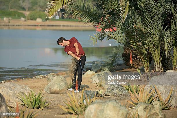 Robert Rock of England plays his second shot at the par 4 14th hole during the first round of the 2014 Abu Dhabi HSBC Golf Championship at Abu Dhabi...