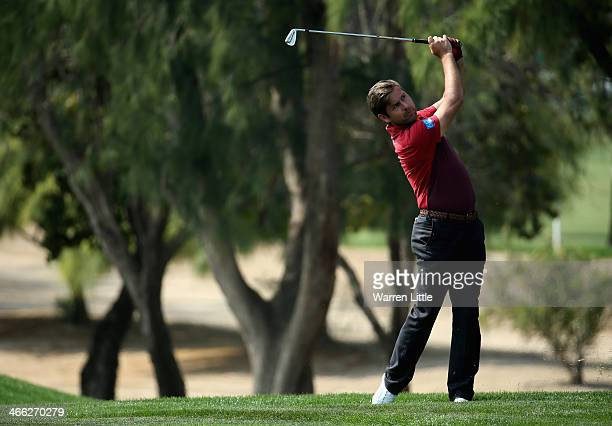 Robert Rock of England plays his second shot into the first green during the third round of the 2014 Omega Dubai Desert Classic on the Majlis Course...