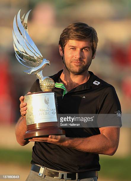 Robert Rock of England poses with the trophy after winning the Abu Dhabi HSBC Golf Championship at the Abu Dhabi Golf Club on January 29 2012 in Abu...