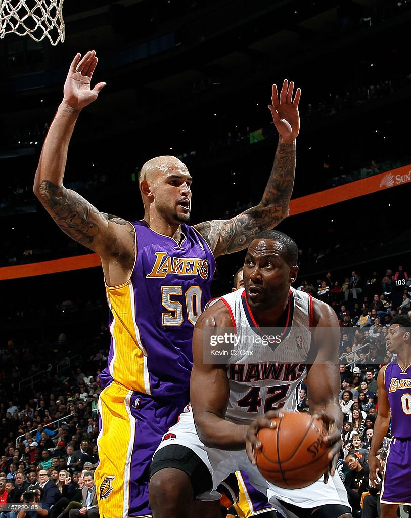 <a gi-track='captionPersonalityLinkClicked' href=/galleries/search?phrase=Robert+Sacre&family=editorial&specificpeople=4682421 ng-click='$event.stopPropagation()'>Robert Sacre</a> #50 of the Los Angeles Lakers defends against <a gi-track='captionPersonalityLinkClicked' href=/galleries/search?phrase=Elton+Brand&family=editorial&specificpeople=201501 ng-click='$event.stopPropagation()'>Elton Brand</a> #42 of the Atlanta Hawks at Philips Arena on December 16, 2013 in Atlanta, Georgia.