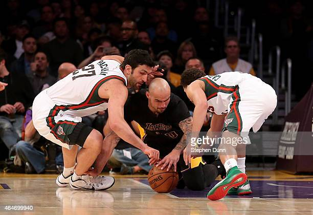 Robert Sacre of the Los Angeles Lakers dives for a loose ball against Zaza Pachulia and Michael CarterWilliams of the Milwaukee Bucks at Staples...