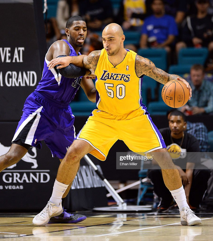 Robert Sacre #50 of the Los Angeles Lakers drives against Jason Thompson #34 of the Sacramento Kings during their preseason game at the MGM Grand Garden Arena on October 10, 2013 in Las Vegas, Nevada. Sacramento won 104-86.
