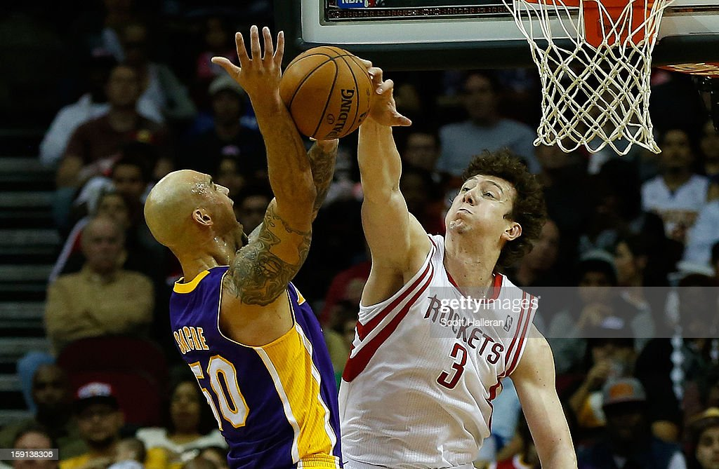 Robert Sacre #50 of the Los Angeles Lakers has a shot blocked by Omer Asik #3 of the Houston Rockets at Toyota Center on January 8, 2013 in Houston, Texas.