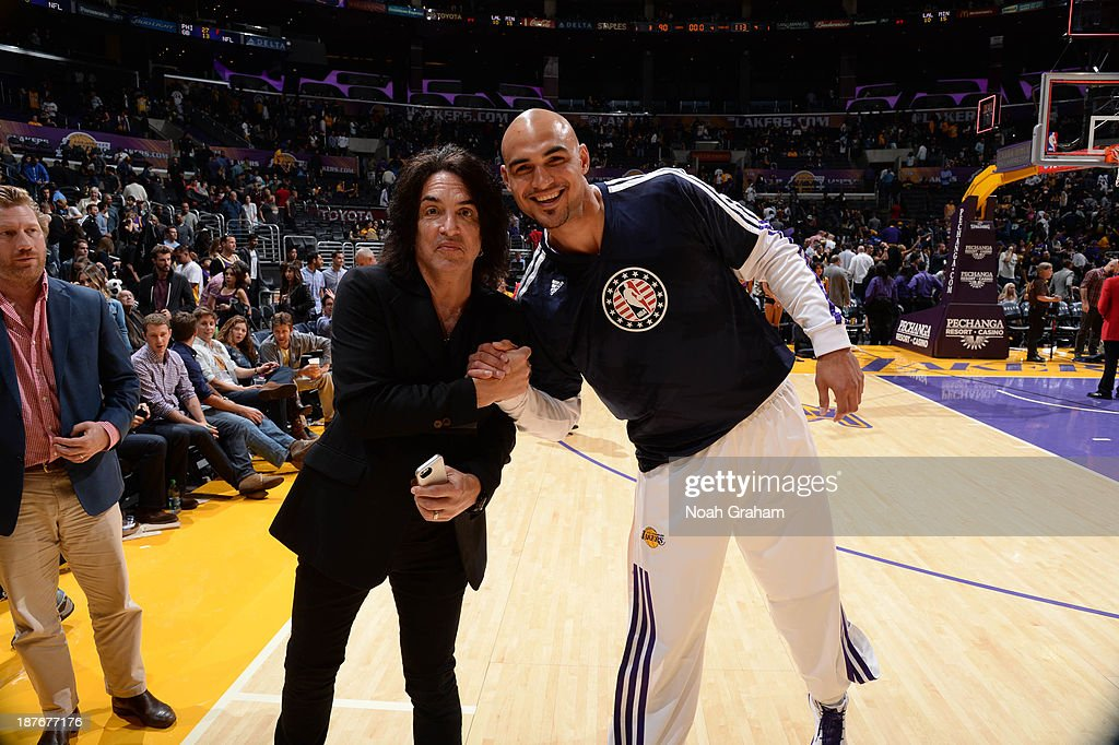 Robert Sacre #50 of the Los Angeles Lakers poses for a photograph with recording artist Paul Stanley after his game against the Minnesota Timberwolves at Staples Center on November 10, 2013 in Los Angeles, California.