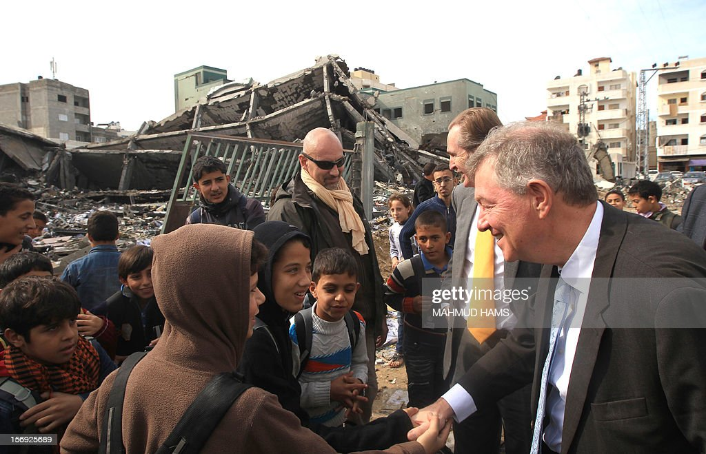 Robert Serry (R), the United Nations Special Coordinator for the Middle East Peace Process, greets children during a visit to survey the damage cause by the Israeli bombardment of the Gaza Strip in reponce to Hamas rocket attacks on Israel, on November 25, 2012, in Gaza City, four days following a truce between Israel and the ruling Hamas movement in Gaza.