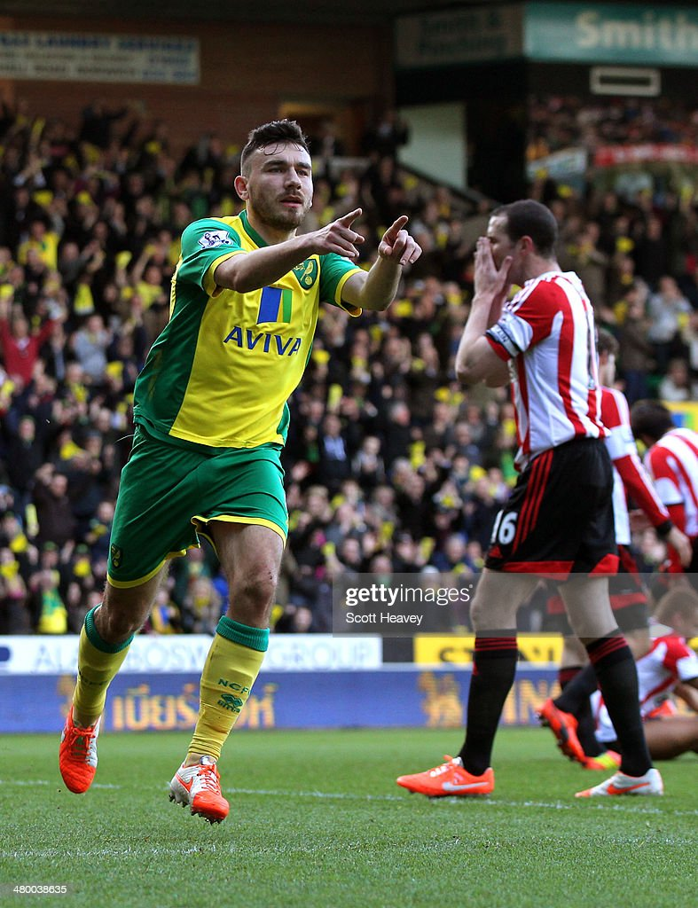 Robert Snodgrass of Norwich City celebrates scoring the opening goal as a dejected John O'Shea of Sunderland reacts during the Barclays Premier League match between Norwich City and Sunderland at Carrow Road on March 22, 2014 in Norwich, England.