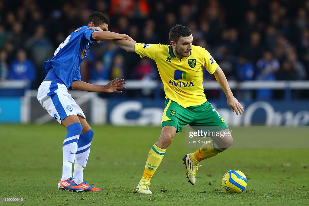 Robert Snodgrass of Norwich City is put under pressure by Kane Ferdinand of Peterborough United during the FA Cup with Budweiser third round match between Peterborough United and Norwich City at London Road Stadium on January 5, 2013 in Peterborough, England.