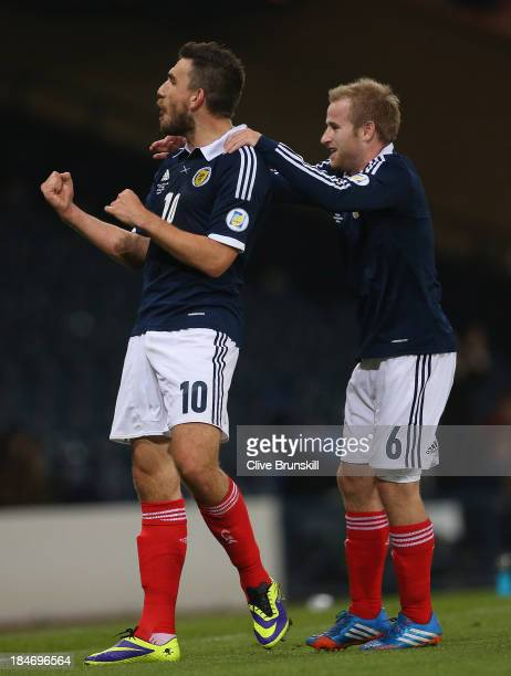 Robert Snodgrass of Scotland celebrates with Barry Bannan after heading the ball past Dejan Lovren of Croatia to score the first goal during the FIFA...