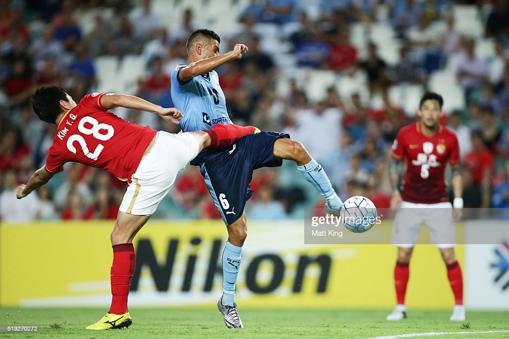 Robert Stambolziev of Sydney FC beats Kim Younggwon of Guangzhou Evergrande to score the first goal during the AFC Champions League match between...