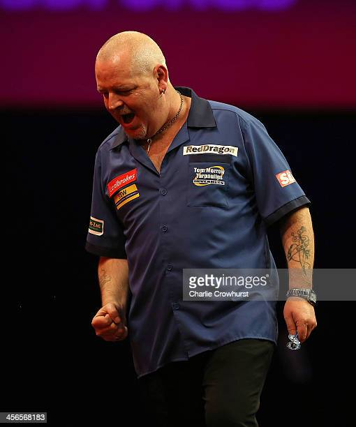 Robert Thornton of Scotland celebrates winning his first round match against Max Hopp of Germany during the Ladbrokescom World Darts Championship on...