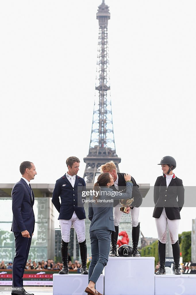 Robert Triefus and Charlotte Casiraghi congratulate the Winners of the 'Gucci Gold Cup Paris Eiffel Jumping Table A against the clock with jump-off ' (L-R) Maikel van der Vleuten (2nd rank), Marcus Ehning (1st rank) and Reed Kessler (3rd rank) aknowledge the applause of the audience during the Paris Eiffel Jumping presented by Gucci at Champ-de-Mars on July 6, 2014 in Paris, France.