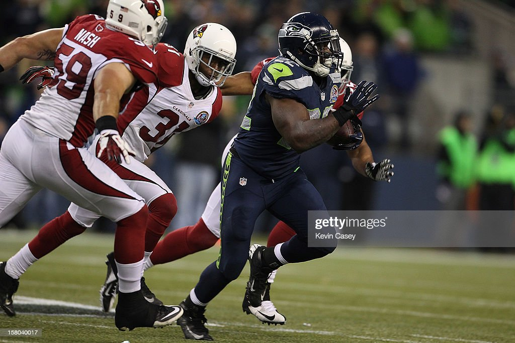Robert Turbin #22 of the Seattle Seahawks outruns three Arizona Cardinals defender in the second half at CenturyLink Field on December 9, 2012 in Seattle, Washington.