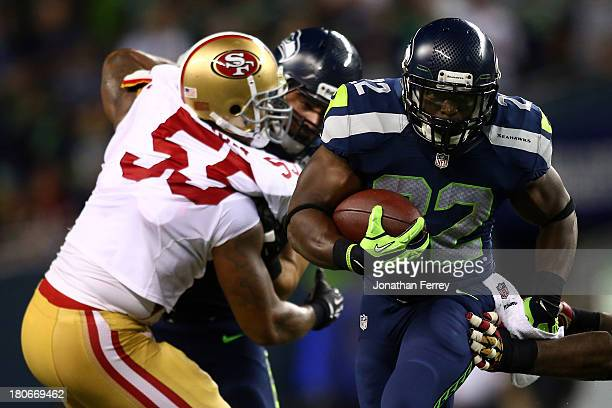 Robert Turbin of the Seattle Seahawks runs the ball against Ahmad Brooks of the San Francisco 49ers during their game at Qwest Field on September 15...