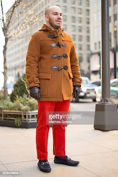 Robert Valente is seen on Michigan Avenue wearing a rust wool Burberry coat red RL Polo pants and black suede Ferragamo shoes on December 19 2015 in...