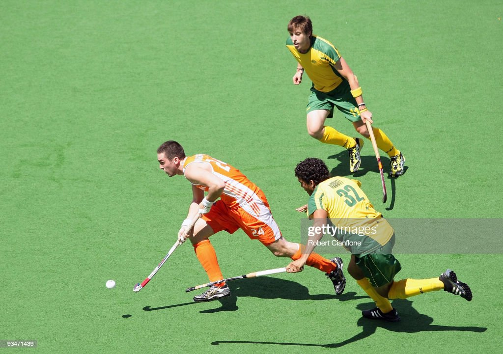 Robert Van Der Horst of the Netherlands is chased by Edward Ockenden and Desmond Abbott of Australia during the match between Australia and the...