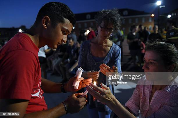 Robert Vied lights candles for other mourners participating in a candlelight vigil on the campus of Louisiana Lafayette on July 24 2015 in Lafayette...