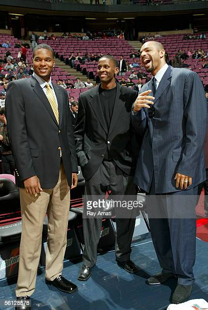 Robert Whaley CJ Miles and Carlos Boozer of the Utah Jazz stand by the bench in dress code before the game against the New Jersey Nets at the...