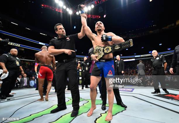 Robert Whittaker of New Zealand celebrates his victory over Yoel Romero of Cuba in their interim UFC middleweight championship bout during the UFC...