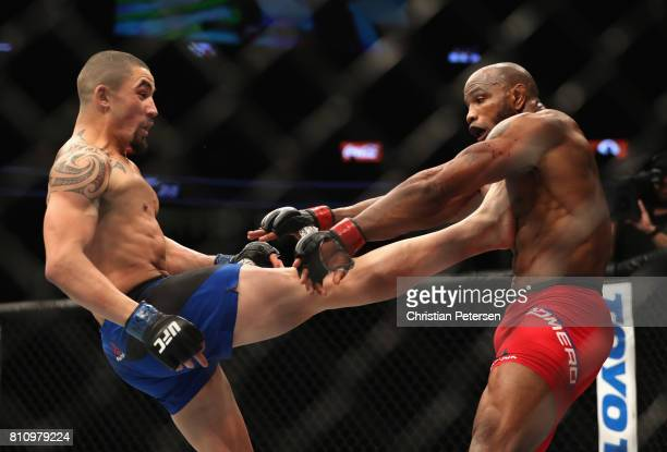 Robert Whittaker of New Zealand kicks Yoel Romero of Cuba in their interim UFC middleweight championship bout during the UFC 213 event at TMobile...
