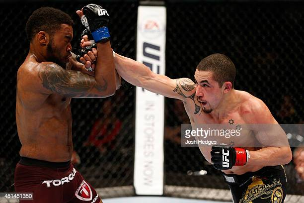 Robert Whittaker punches Mike Rhodes in their welterweight fight during the UFC Fight Night event at Vector Arena on June 28 2014 in Auckland New...