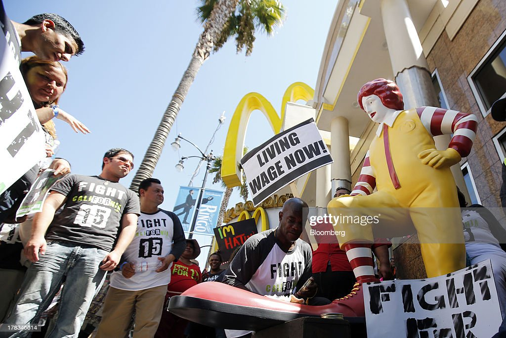 Robert Wideman, a maintenance mechanic at McDonalds Corp., shines the shoes of a Ronald McDonald statue outside of a restaurant while protesting with fast-food workers and supporters organized by the Service Employees International Union (SEIU) in Los Angeles, California, U.S., on Thursday, Aug. 29, 2013. Fast-food workers in 50 U.S. cities plan to walk off the job today, ratcheting up pressure on the industry to raise wages and demanding the right to wages of $15 an hour, more than double the federal minimum of $7.25. Photographer: Patrick T. Fallon/Bloomberg via Getty Images