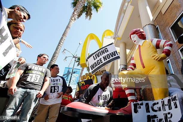 Robert Wideman a maintenance mechanic at McDonalds Corp shines the shoes of a Ronald McDonald statue outside of a restaurant while protesting with...