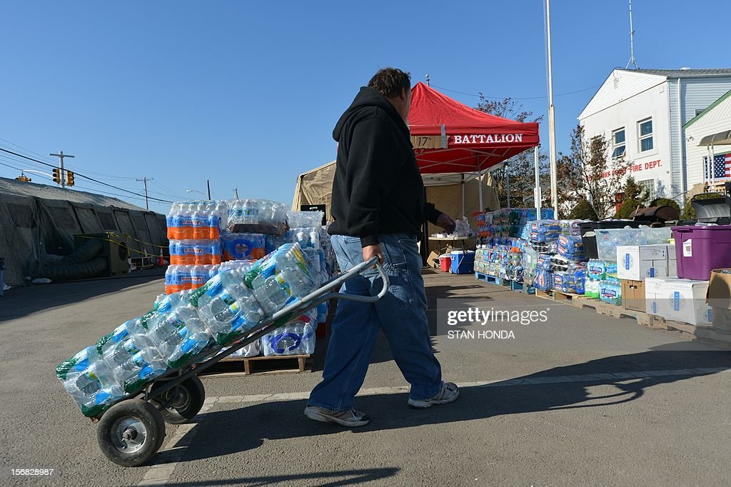 Robert Willis carries water to a distribution point in the Breezy Point neighborhood in the Rockaways section of Queenson November 22, 2012 in New York as the city recovers from the effects of superstorm Sandy. AFP PHOTO/Stan HONDA