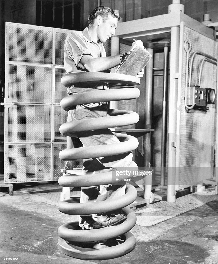 Robert Wilson takes notes during an inspection of a giant spring coil which will be used in the underground Atlas missile sites. Chicago, November 21, 1963.