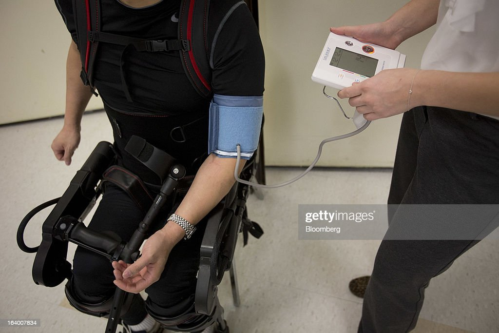 Robert Woo, 45, gets his blood pressure taken while sitting on a chair in an Ekso Bionics 'exoskeleton,' at Mount Sinai Medical Center in New York, U.S., on Thursday, March 14, 2013. Wearable machines that enhance human muscle power are poised to leave the realm of science fiction and help factory workers hoist heavier tools, lighten soldiers' loads and enable spinal patients to walk. Photographer: Scott Eells/Bloomberg via Getty Images