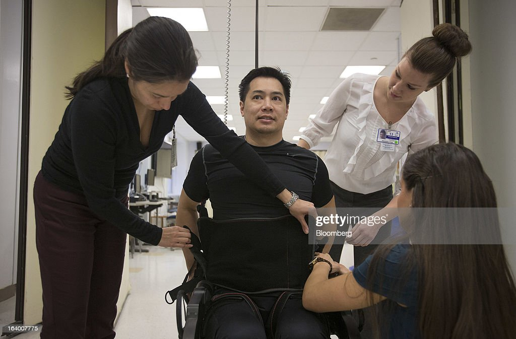 Robert Woo, 45, is helped into an Ekso Bionics 'exoskeleton,' at Mount Sinai Medical Center in New York, U.S., on Thursday, March 14, 2013. Wearable machines that enhance human muscle power are poised to leave the realm of science fiction and help factory workers hoist heavier tools, lighten soldiers' loads and enable spinal patients to walk. Photographer: Scott Eells/Bloomberg via Getty Images