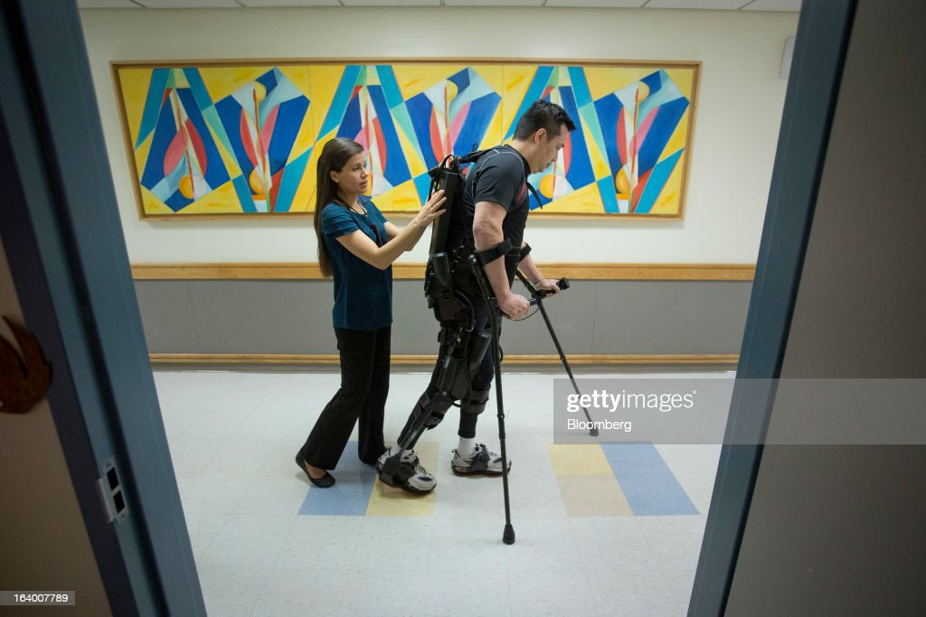 Robert Woo, 45, right, walks with the aid of an Ekso Bionics 'exoskeleton,' and his physical therapist Shantel Firpi, at Mount Sinai Medical Center in New York, U.S., on Thursday, March 14, 2013. Wearable machines that enhance human muscle power are poised to leave the realm of science fiction and help factory workers hoist heavier tools, lighten soldiers' loads and enable spinal patients to walk. Photographer: Scott Eells/Bloomberg via Getty Images