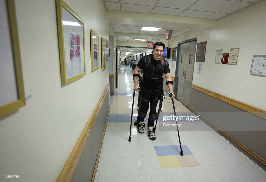 Robert Woo, 45, walks with the aid of an Ekso Bionics 'exoskeleton,' at Mount Sinai Medical Center in New York, U.S., on Thursday, March 14, 2013. Wearable machines that enhance human muscle power are poised to leave the realm of science fiction and help factory workers hoist heavier tools, lighten soldiers' loads and enable spinal patients to walk. Photographer: Scott Eells/Bloomberg via Getty Images