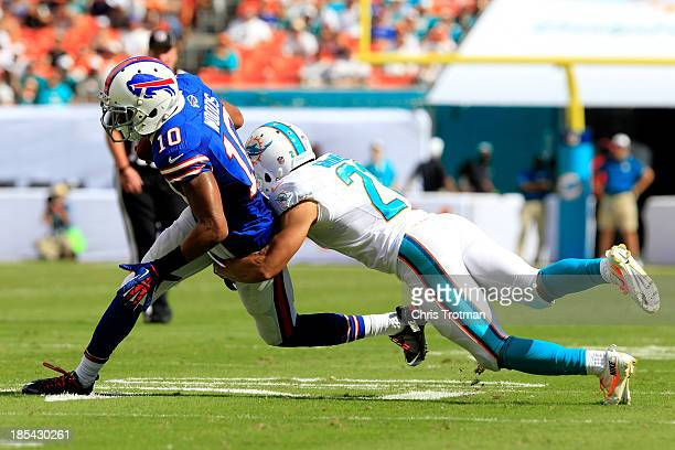 Robert Woods of the Buffalo Bills is tackled by Leodis McKelvin of the Buffalo Bills at Sun Life Stadium on October 20 2013 in Miami Gardens Florida