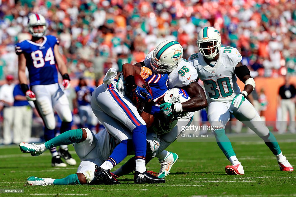 Robert Woods #10 of the Buffalo Bills is tackled by <a gi-track='captionPersonalityLinkClicked' href=/galleries/search?phrase=Reshad+Jones&family=editorial&specificpeople=4511449 ng-click='$event.stopPropagation()'>Reshad Jones</a> #20 of the Miami Dolphins and <a gi-track='captionPersonalityLinkClicked' href=/galleries/search?phrase=Dion+Jordan&family=editorial&specificpeople=6161243 ng-click='$event.stopPropagation()'>Dion Jordan</a> #95 of the Miami Dolphins at Sun Life Stadium on October 20, 2013 in Miami Gardens, Florida.