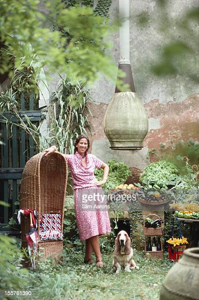 Roberta di Camerino Zanga poses by a covered wicker chair alongside a basset hound dog on her mother's island retreat in Venice Italy in September...