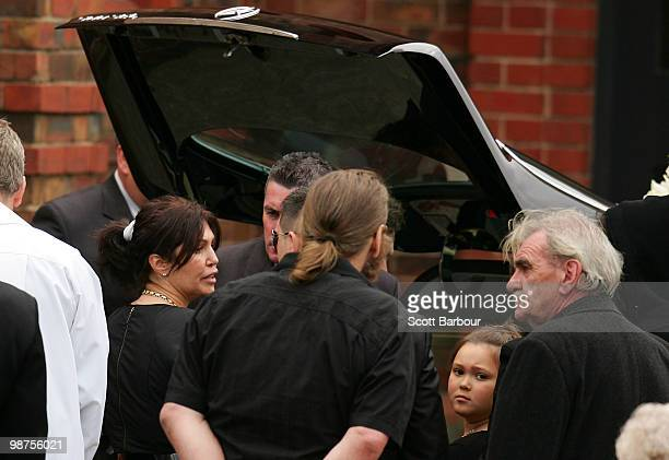 Roberta Williams exwife of Carl Williams and her daughter Dhakota Williams look on after the coffin is placed in the back of the hearse after the...