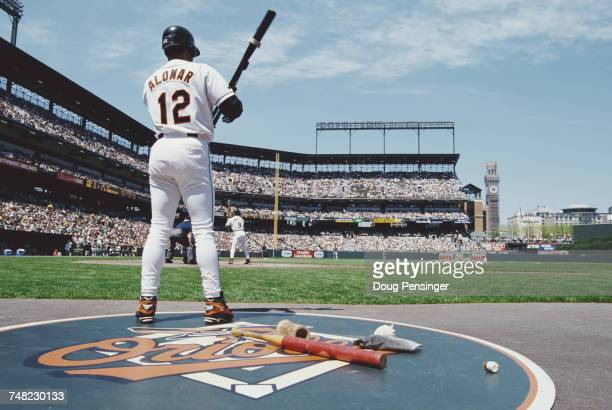 Roberto Alomar and second baseman for the Baltimore Orioles warms up in the on deck circle as Brady Anderson bats at the plate during the Major...