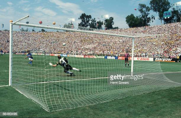Roberto Baggio of Italy watches his penalty kick go over the crossbar as Brazilian goalkeeper Claudio Taffarel dives the wrong way during the penalty...