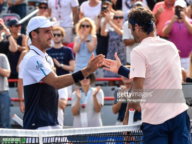 Roberto Bautista Agut of Spain congratulates Roger Federer of Switzerland for his victory during day eight of the Rogers Cup presented by National...