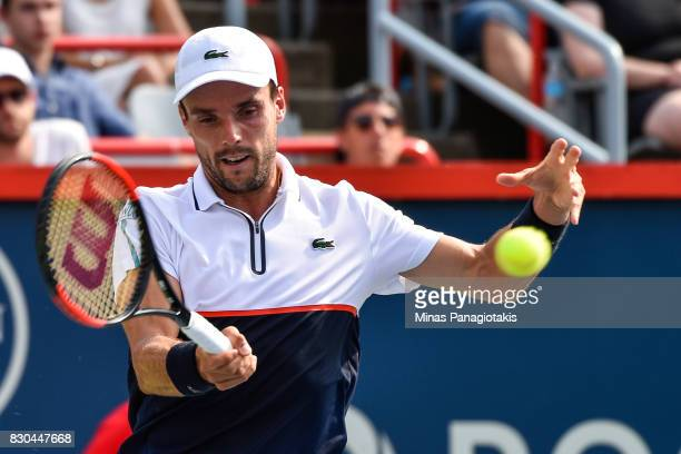 Roberto Bautista Agut of Spain hits a return against Roger Federer of Switzerland during day eight of the Rogers Cup presented by National Bank at...