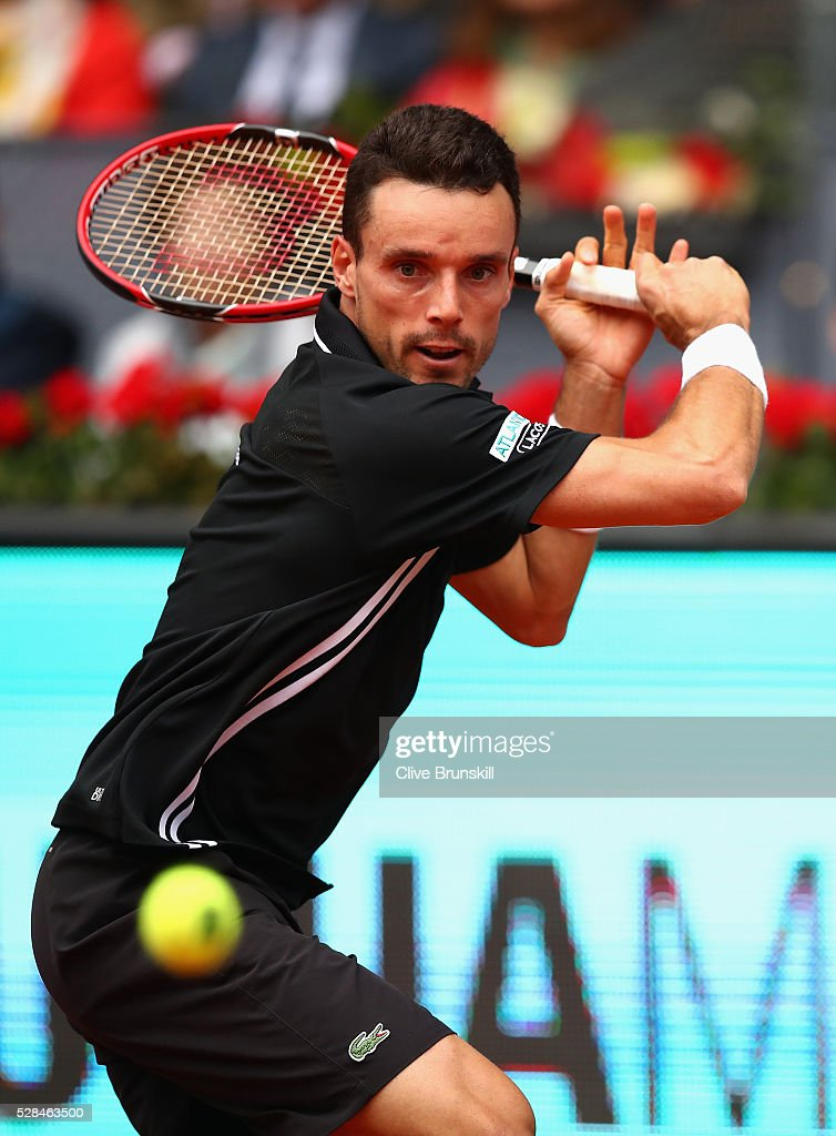 Roberto Bautista Agut of Spain plays a backhand against Novak Djokovic of Serbia in their third round match during day six of the Mutua Madrid Open tennis tournament at the Caja Magica on May 05, 2016 in Madrid,Spain