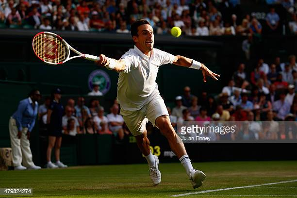 Roberto Bautista Agut of Spain returns a serve in his Gentlemen's Singles Fourth Round match against Roger Federer of Switzerland during day seven of...
