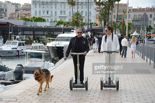 Roberto Cavalli and Lina Nilson ride on segways on day 8 of the 67th Annual Cannes Film Festival on May 21 2014 in Cannes France