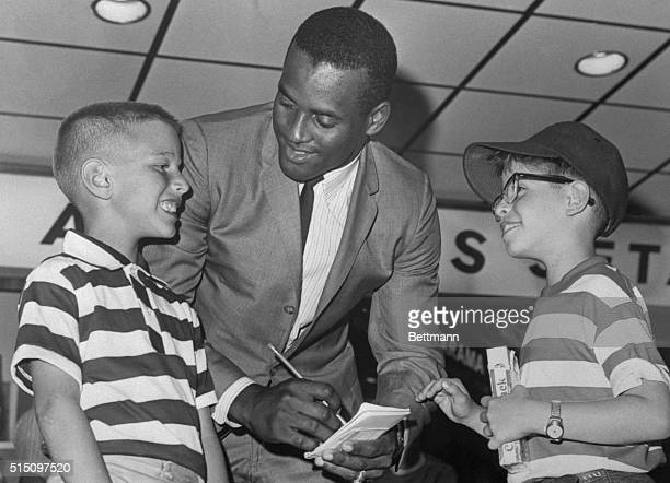 Roberto Clemente right fielder for the Pittsburgh Pirates sign autographs for left to right Johnny Sloan and Alvin Green both of Brooklyn New York...