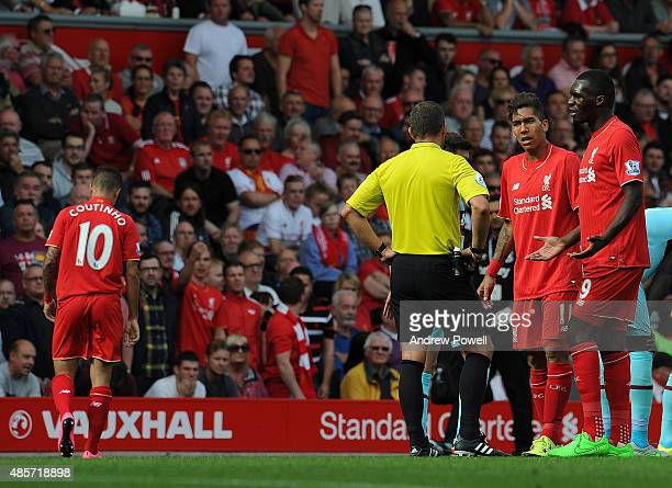 Roberto Firmino and Christian Benteke of Liverpool talk to referee Kevin Friend as Philippe Coutinho walks off the pitch after recieving a red card...