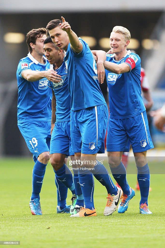 Roberto Firmino of Hoffenheim (L) celebrates his team's first goal with his team mates Niklas Suele (C) and Andreas Beck (R) during the Bundesliga match between 1899 Hoffenheim and Hamburger SV at Wirsol Rhein-Neckar Arena Sinsheim on February 1, 2014 in Sinsheim, Germany.