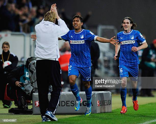 Roberto Firmino of Hoffenheim celebrates with Coach Markus Gisdol and teammate Sebastian Rudy after scoring their team's second goal during the...