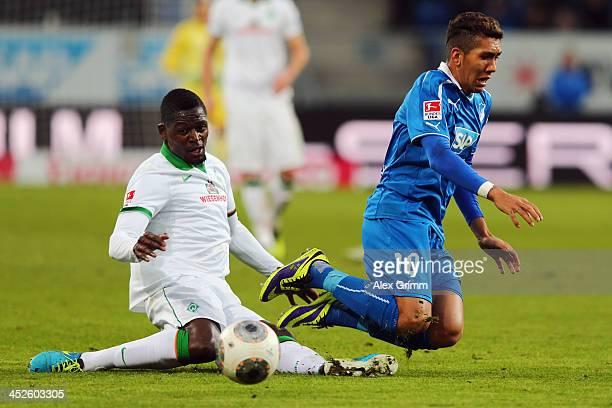 Roberto Firmino of Hoffenheim is challenged by Cedric Makiadi of Bremen during the Bundesliga match between 1899 Hoffenheim and Werder Bremen on...