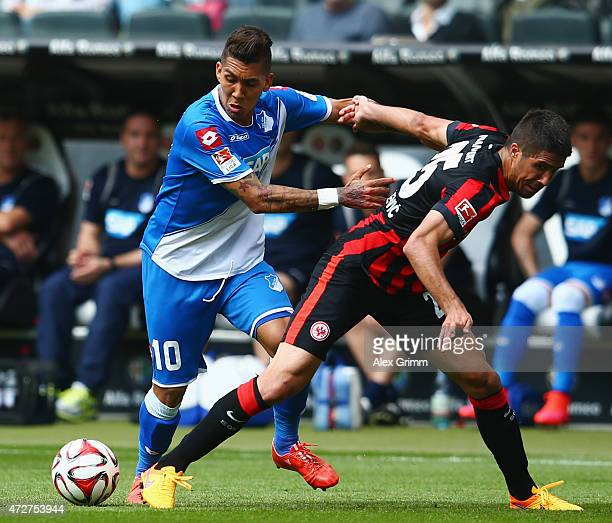 Roberto Firmino of Hoffenheim is challenged by Slobodan Medojevic of Frankfurt during the Bundesliga match between Eintracht Frankfurt and 1899...